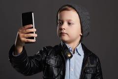 Niño pequeño que hace el selfie Niño divertido con un teléfono Pequeño fotógrafo Fotos de archivo