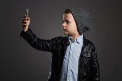 Niño pequeño que hace el selfie Niño divertido con un teléfono Pequeño fotógrafo Foto de archivo libre de regalías