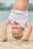 Niño pequeño que hace una posición del pino en la playa Reconstrucción y deportes del verano Imágenes de archivo libres de regalías