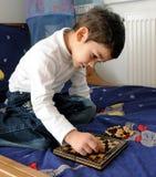 Niño pequeño que juega a ajedrez imagen de archivo