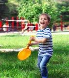 Niño pequeño que juega al muchacho alegre feliz del tenis que sostiene un st de la estafa Imágenes de archivo libres de regalías