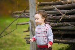 Niño pequeño que juega cerca de los registros Fotos de archivo