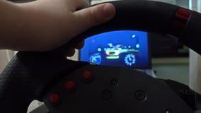 Niño pequeño que juega compitiendo con el juego de ordenador usando el volante Concepto del principiante tiro 4k metrajes