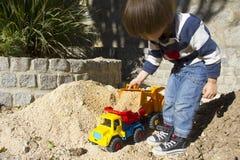 Niño pequeño que juega con el cavador del juguete y el camión de descargador Foto de archivo libre de regalías