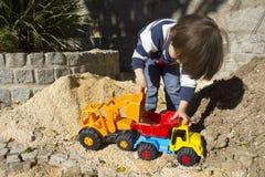 Niño pequeño que juega con el cavador del juguete y el camión de descargador Fotos de archivo
