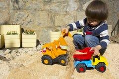 Niño pequeño que juega con el cavador del juguete y el camión de descargador Imagen de archivo