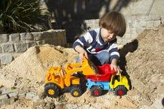 Niño pequeño que juega con el cavador del juguete y el camión de descargador Imágenes de archivo libres de regalías