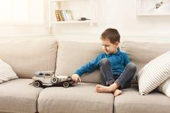 Niño pequeño que juega con el coche del juguete en casa Fotografía de archivo