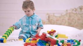Niño pequeño que juega con el diseñador en la cama en el dormitorio Juego del muchacho con un diseñador multicolor Concepto de fe metrajes