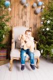 Niño pequeño que juega con el juguete en casa cerca del árbol de navidad Imágenes de archivo libres de regalías