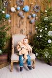 Niño pequeño que juega con el juguete en casa cerca del árbol de navidad Fotografía de archivo