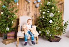 Niño pequeño que juega con el juguete en casa cerca del árbol de navidad Fotografía de archivo libre de regalías