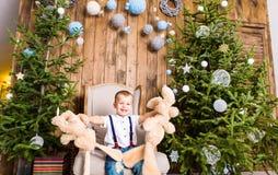 Niño pequeño que juega con el juguete en casa cerca del árbol de navidad Fotos de archivo libres de regalías