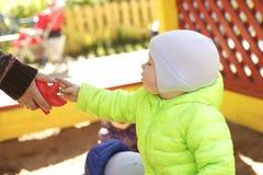 Niño pequeño que juega con el papá en salvadera Imagenes de archivo