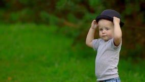 Niño pequeño que juega con el sombrero almacen de metraje de vídeo