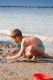 Niño pequeño que juega con la arena en la playa de Italia del mar Fotos de archivo