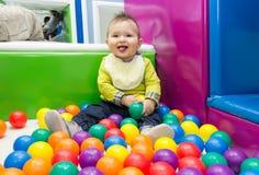 Niño pequeño que juega con las bolas fotografía de archivo