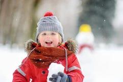 Niño pequeño que juega con las bolas de nieve con el muñeco de nieve en fondo Imagenes de archivo