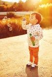 Niño pequeño que juega con las burbujas de jabón fotografía de archivo