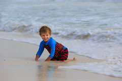 Niño pequeño que juega con las ondas en la playa de la arena Fotografía de archivo
