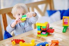 Niño pequeño que juega con los bloques coloridos del plástico en la guardería Foto de archivo libre de regalías