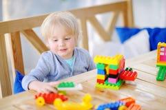 Niño pequeño que juega con los bloques coloridos del plástico en la guardería o en casa Imágenes de archivo libres de regalías