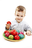 Niño pequeño que juega con los huevos de Pascua en cesta Foto de archivo libre de regalías