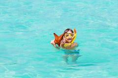 Niño pequeño que juega con los pescados de la estrella en la playa tropical Imagen de archivo libre de regalías