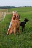 Niño pequeño que juega con su perro imagen de archivo