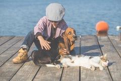 Niño pequeño que juega con su perro y gato por el río imagenes de archivo