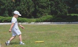 Niño pequeño que juega el disco volador en el parque imagenes de archivo