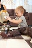Niño pequeño que juega en cocina Imágenes de archivo libres de regalías