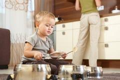 Niño pequeño que juega en cocina foto de archivo libre de regalías
