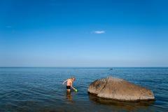 Niño pequeño que juega en el agua cerca de la playa foto de archivo libre de regalías