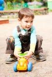 Niño pequeño que juega en el coche del juguete Fotografía de archivo