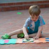 Niño pequeño que juega en el patio trasero Imagenes de archivo