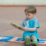 Niño pequeño que juega en el patio trasero Fotos de archivo