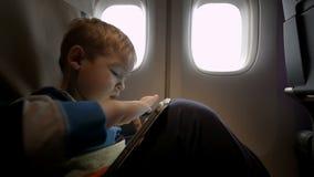 Niño pequeño que juega en la almohadilla táctil en el avión almacen de metraje de vídeo