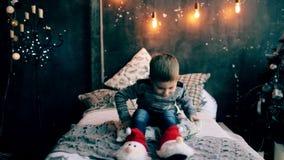 Niño pequeño que juega en la cama en la Navidad almacen de video