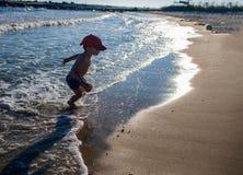 Niño pequeño que juega en la costa Foto de archivo libre de regalías