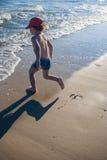 Niño pequeño que juega en la costa Imagen de archivo