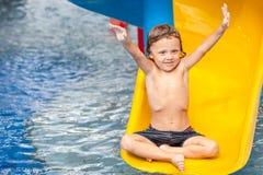 Niño pequeño que juega en la piscina en diapositiva Imagenes de archivo