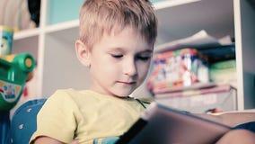 Niño pequeño que juega en la tableta almacen de metraje de vídeo