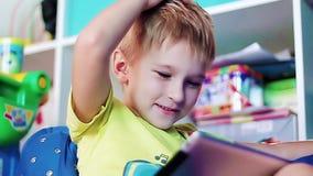 Niño pequeño que juega en la tableta almacen de video