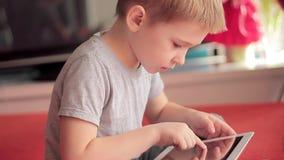 Niño pequeño que juega en los juegos de tableta almacen de video