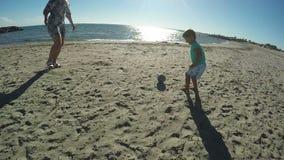 Niño pequeño que juega a fútbol en la playa almacen de metraje de vídeo