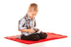 Niño pequeño que juega a juegos en smartphone Fotos de archivo