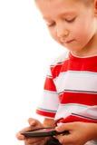 Niño pequeño que juega a juegos en smartphone Imagenes de archivo