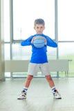 Niño pequeño que juega la bola y la forma azules del baloncesto Imagen de archivo