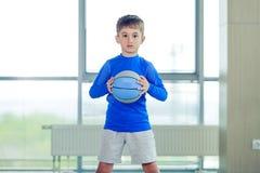 Niño pequeño que juega la bola y la forma azules del baloncesto Imágenes de archivo libres de regalías